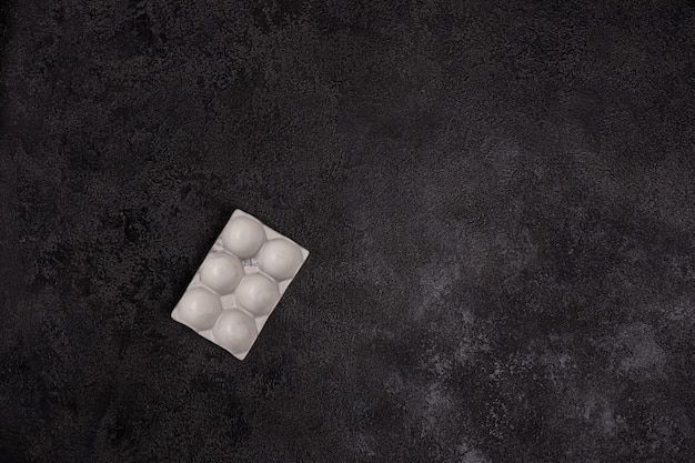Egg stand made of white concrete on a black textured background.