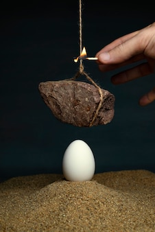Egg under a stone hanging on a rope