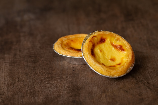 Egg tarts in aluminum foil cup on wood table,  traditional portuguese dessert served in coffee shop