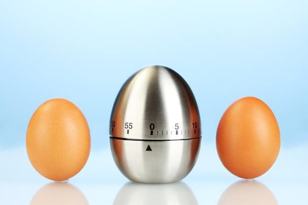 青いテーブルの上の卵タイマーと卵