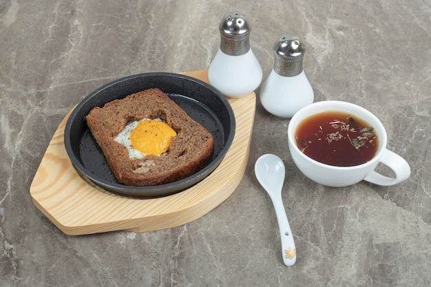 スパイスと大理石の上の卵トーストパンとお茶。高品質の写真