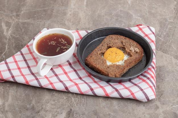 Яичный тостовый хлеб и чашка чая на скатерти. фото высокого качества