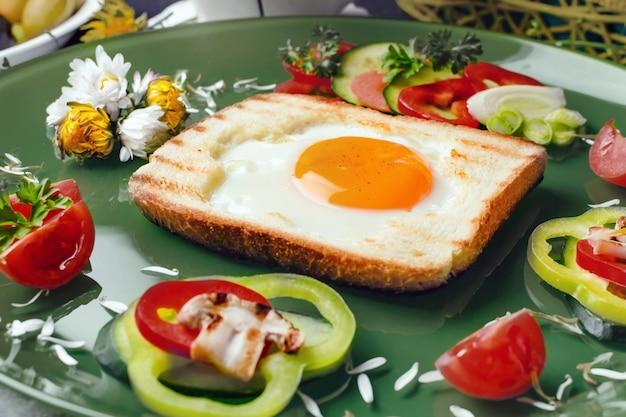 Uovo in pane tostato cotto con verdure fresche