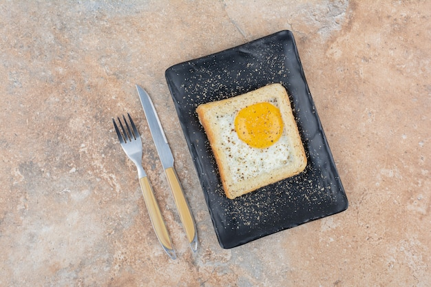 Egg toast with spices on black plate with cutlery