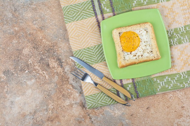 Egg toast with spices on green plate with cutlery and tablecloth