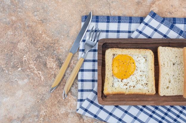 Toast all'uovo con spezie sul piatto di legno con posate