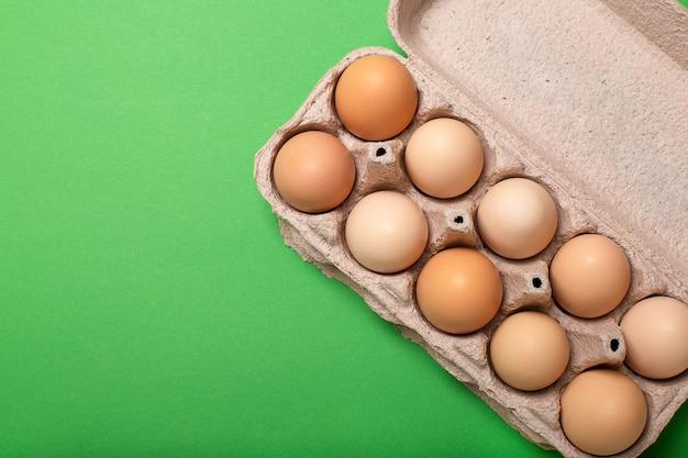 明るい緑の背景、コピースペース、トップビューで卵トレイ