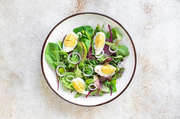 卵野菜サラダ緑の葉はテーブルの上にほうれん草のルッコラレタスを混ぜる健康的な食べ物