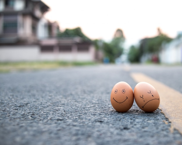 Egg with drawn sad face near happy ones on roadway. threat of depression