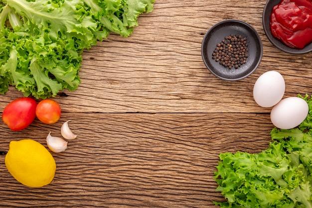 素朴な天然木の質感の背景にケチャップ、コショウ、レタス、トマト、ニンニク、レモン、食材、上面図と卵