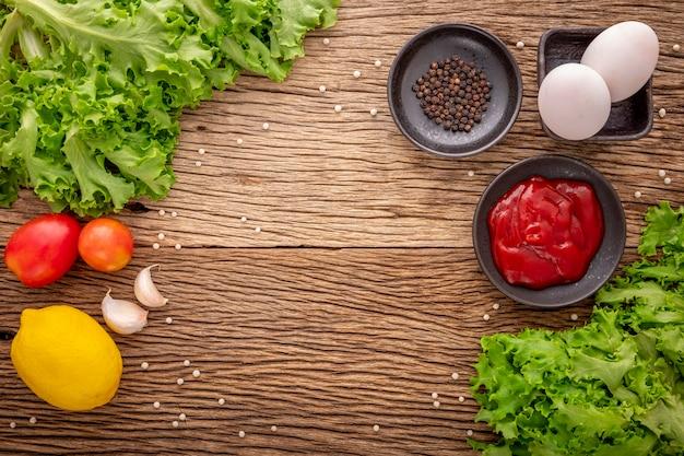 素朴な天然木の質感の背景にケチャップ、コショウ、レタス、トマト、ニンニク、レモン、食材、上面図の卵