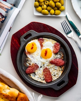 Egg with sausage in pan olives top view