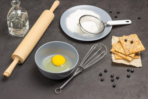 Яичный желток в миске. бумага, металлический венчик и печенье. муку и сито на серой тарелке. готовка. черный фон. вид сверху