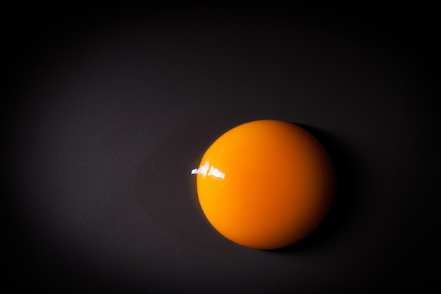 Egg yolk isolated on black background with space for copy