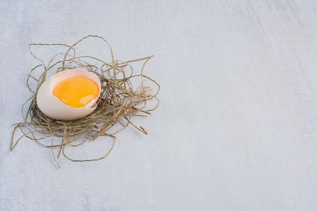 Tuorlo d'uovo nel guscio su un piccolo mucchio di paglia sul tavolo di marmo.