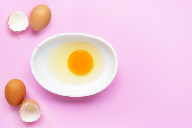 Egg yolk and white in a bowl on pink.