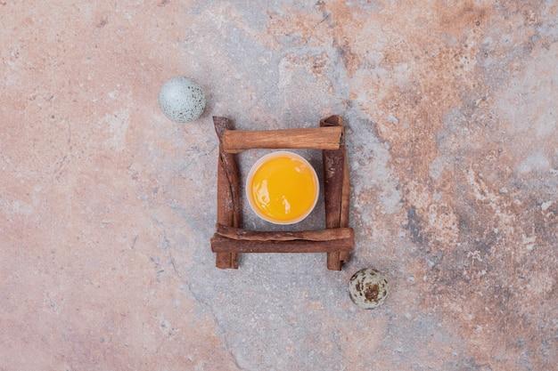 Egg yolk with cinnamons and quails eggs on marble surface.