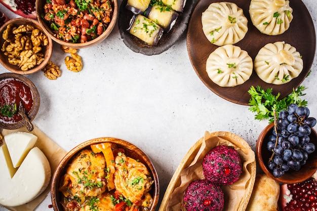 伝統的なジョージア料理のテーブル。ヒンカリ、ファリ、チャホフビリ、ロビオ、チーズ、egg子は白いテーブルにロールバックします。