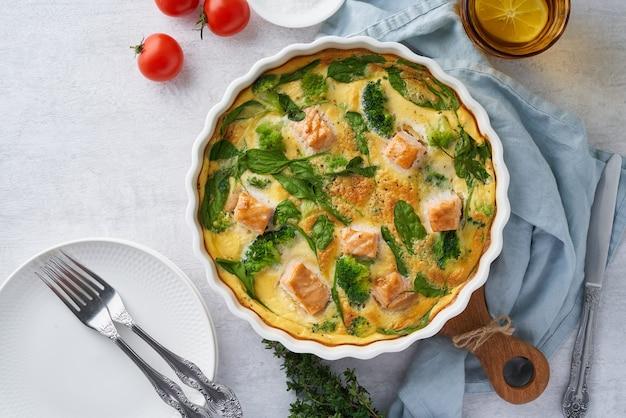 サーモンブロッコリーとほうれん草のトップビューコピースペースを添えた卵ベースのフリッタータオムレツ