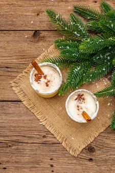 Eggnog cocktail in two glasses arranged with christmas decoration on old wooden table. evergreen fer tree branch, artificial snow, sackcloth napkin