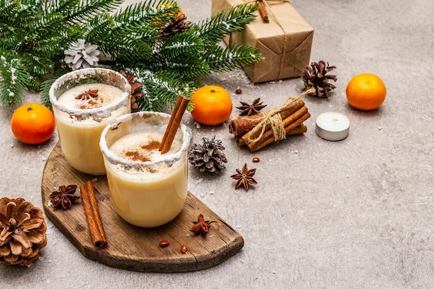 Яйцо с корицей и мускатным орехом для рождественских и зимних праздников. домашний напиток в очках с острым ободком. мандарины, свечи, подарок.