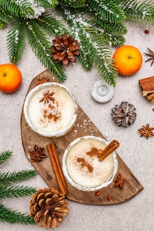 Eggnog with cinnamon and nutmeg for christmas and winter holidays. homemade beverage in glasses with spicy rim. tangerines, candles, gift.