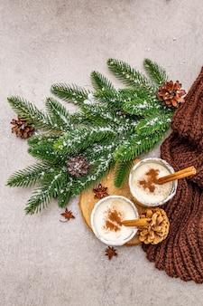 Домашнее eggnog с корицей в стекле. типичный рождественский десерт. вечнозеленые еловые ветки, шишки, уютный плед, искусственный снег.