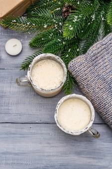 Eggnog коктейль в кружку двух стаканов, аранжировано с рождественские украшения на светлом деревянном столе. вечнозеленая еловая ветка, подарок, уютный трикотаж, искусственный снег