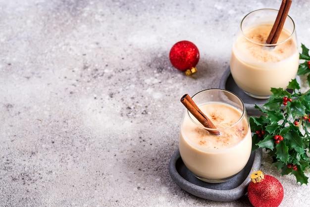 Новогодний или рождественский коктейль eggnog, горячий зимний или осенний напиток с корицей и мускатным орехом в бокале на светлом камне, праздничное оформление