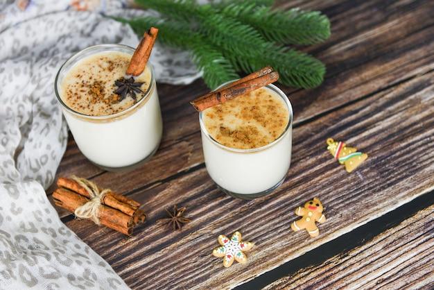 Вкусные праздничные напитки eggnog, такие как тематические вечеринки с корицей и мускатным орехом для традиционных рождественских и зимних праздников домашний эгног из бокалов и конфета украшенный стол с сосновыми листьями