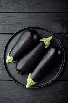 ナス、茄子の有機熟した全野菜セット、黒い木製のテーブル