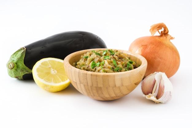 Eggplant baba ganoush and ingredients isolated on white