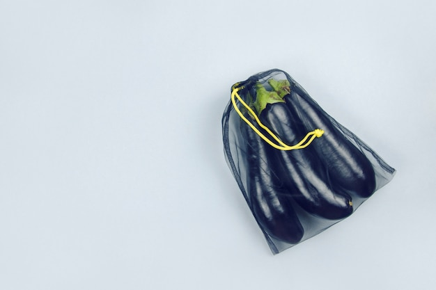 Eggplant in a black grocery bag on a gray background