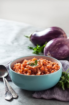 Eggplant caviar in blue bowl and fresh vegetables on background. copy space