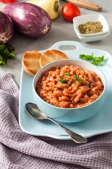 Eggplant caviar in blue bowl and fresh vegetables on background.