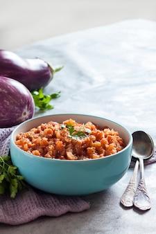 青いボウルに茄子のキャビアと背景に新鮮な野菜。コピースペース
