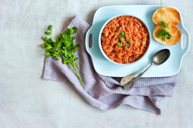 青いボウルに茄子のキャビアと背景に新鮮な野菜。フラットレイ、上面図、コピースペース