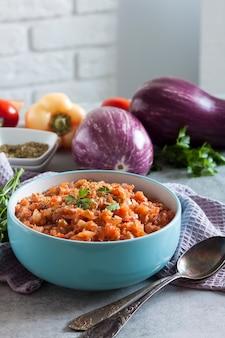 青いボウルに茄子のキャビアと背景に新鮮な野菜。
