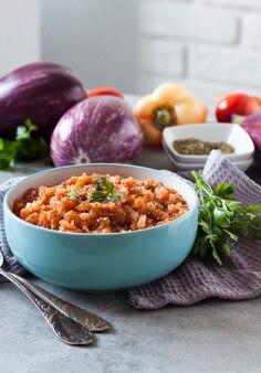 青いボウルに茄子のキャビア、背景に新鮮な野菜。