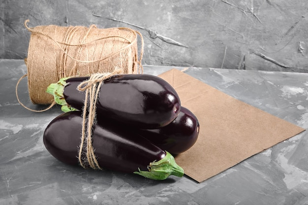 Eggplant on a gray background, behind paper bags and heather for packaging