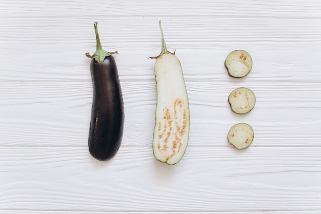 Eggplant is shredded on the white wooden background, top view.