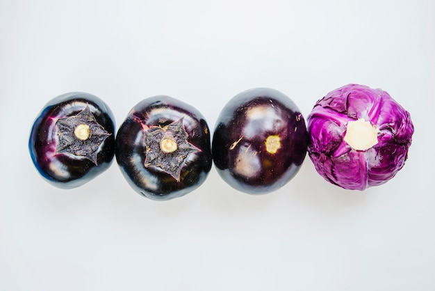 Eggplant and purple cabbage arranged on white background