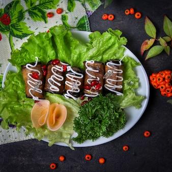 Рулетики из баклажанов в тарелке с зеленью, майонезом, сыром, фруктами, листьями