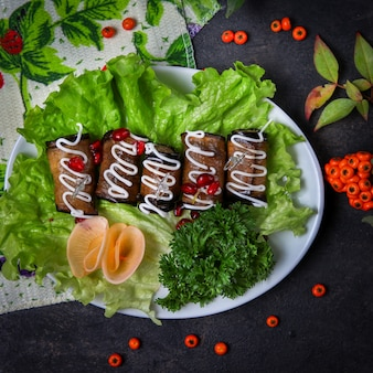Eggplant rolls in a plate with herbs, mayonnaise, cheese, fruits, leaves