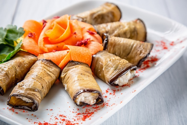 Eggplant rolls with cheese and carrots on white plate with selective focus
