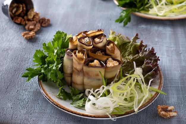 Рулетики из баклажанов с сыром, чесноком и грецкими орехами на тарелке. вкусная закуска из баклажанов