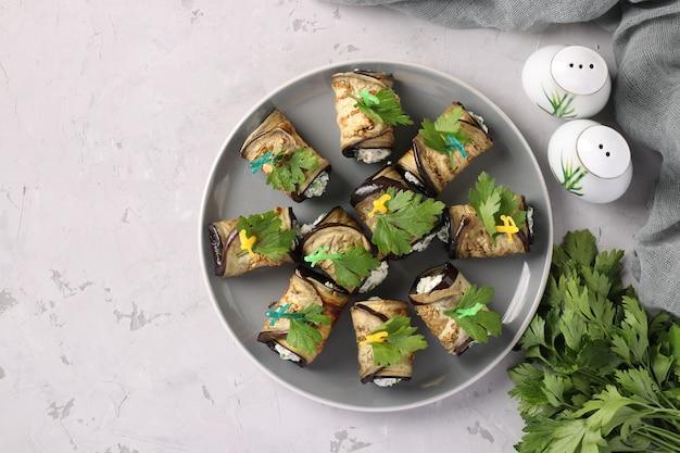 Рулетики из баклажанов с чесноком и сливочным сыром на тарелке на светло-сером фоне