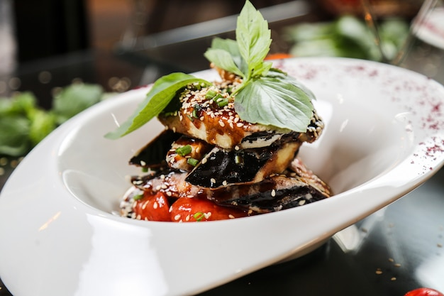 Eggplant with herbs topped with sesame seed close-up view