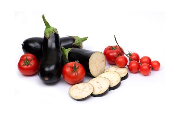 Баклажаны с мелкими помидорами. баклажаны, изолированные на белом фоне с помидорами.