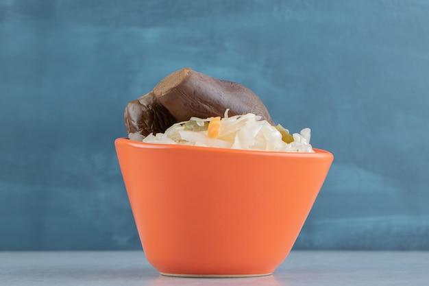 대리석 표면에 있는 그릇에 가지와 소금에 절인 양배추 무료 사진